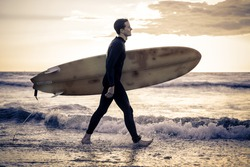 Surfer with board walking along the ocean - Sportive man going to surf on a tropical beach