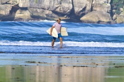 surfer with broken surfboard