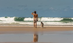 Surfer with his dog watching to the ocean