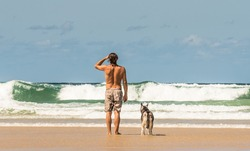 Surfer with his dog watching to the ocean. Close up