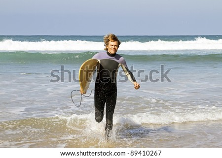 Surfer with his surfboard running out of the water from the atlantic ocean