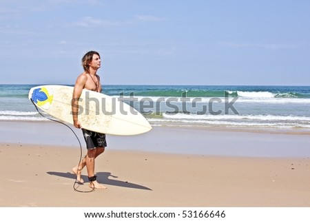 Surfer with his surfboard walking along the beach