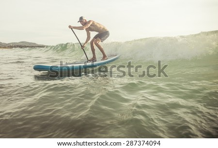 surfer with paddle board catching the wave. concept about sport and people