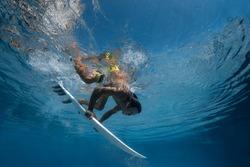 Surfer with surf board dive underwater with fun under big ocean wave