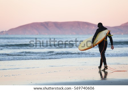 Surfer with surfboard and wetsuit walks towards the water at sunrise in Pismo Beach Zdjęcia stock ©