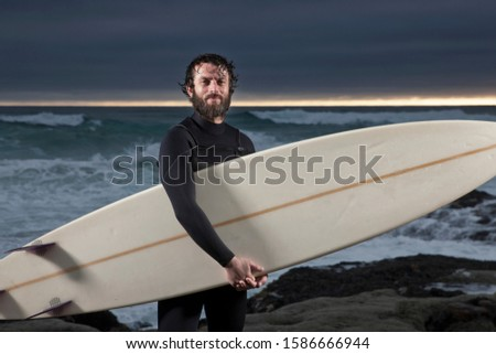 Surfer with surfboard standing on rocks wearing wetsuit with ocean in background and dramatic mood sky