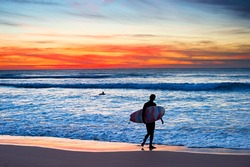 Surfer with surfboard walking on the beach at majestic sunset