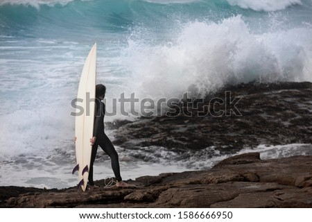 Surfer with surfboard wearing wetsuit watching ocean waves crash over rocks
