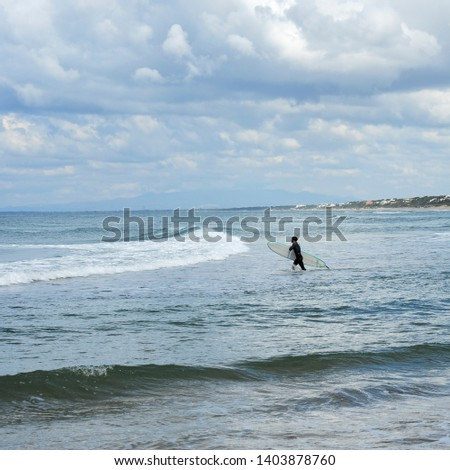 Surfer with the wetsuit diving in blue sea with his surfboard. #1403878760