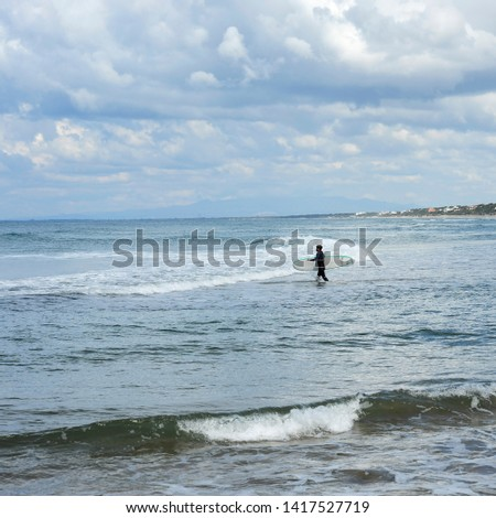 Surfer with the wetsuit diving in blue sea with his surfboard. #1417527719