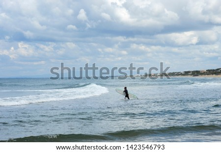 Surfer with the wetsuit diving in blue sea with his surfboard. #1423546793