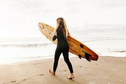 Surfer woman walking into the sea with yellow surfboard on the beach at sunrise light