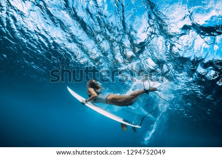 Surfer woman with surfboard dive underwater with ocean wave.