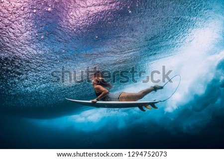 Surfer woman with surfboard dive underwater with under ocean waves.