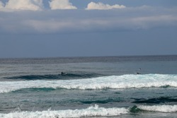 Surfers are waiting for a convenient wave on their surfboards. Tropical surfers paradise with Nyang Nyang beach on Bali island. Azure blue sky, sunny day. Wild waves are approaching the shore in rows.