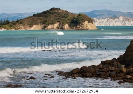 Surfers at Sponge Bay Island, Gisborne, New Zealand