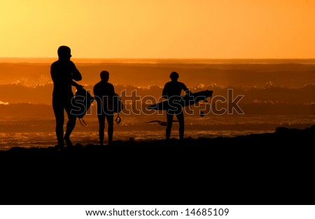 Surfers at sunset - stock photo