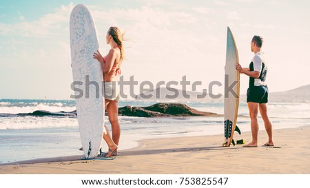 Surfers couple waiting for the high waves on beach - Sporty people with surf boards on the beach - Extreme sport and vacation concept - Soft ocus on female head - Vintage filter