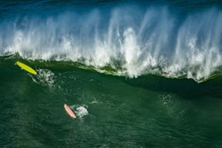 Surfers duck diving in a wave, Basque Country