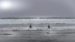 Surfers heading into the Waves in the Dense Fog to surf in Cox Bay at the Pacific Rim National Park on Vancouver Island, British Columbia, Canada