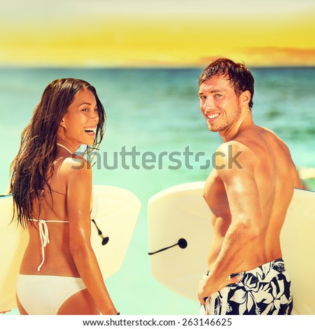 Surfers on beach having fun in summer. Surfer woman and man with boogieboard smiling happy on beach on Hawaii. Multiracial couple Asian woman and Caucasian man in outdoor water activity during travel.