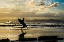 Surfers on the beach. Sunset on the Gold Coast, Australia.
