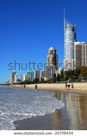 SURFERS PARADISE - 8 September 2006: Holiday-makers take an early morning stroll on the beach at Surfers Paradise, Queensland, Australia on 8 September 2006.