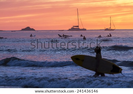Surfers silhouetted against a brillinatly colored sunset  on Playa Tamarindo, Guanacaste, Costa Rica #241436146