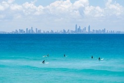 Surfers sit on their boards in front of the Surfer's Paradise skyline, Gold Coast, Queensland, Australia.