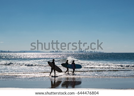 Surfers walking to the surf, with Surfers Paradise on the background - Gold Coast, Australia. (Colour) #644476804