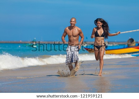 surfig couple posing on the beach