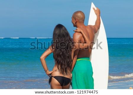 surfig couple posing on the beach