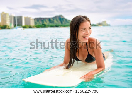 Surfing Asian woman surfer girl on surf lesson in Hawaii paddling on surfboard in ocean. Sexy sports athlete training in water. Watersport active lifestyle. #1550229980