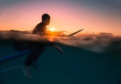 Surfing at Sunrise with underwater view