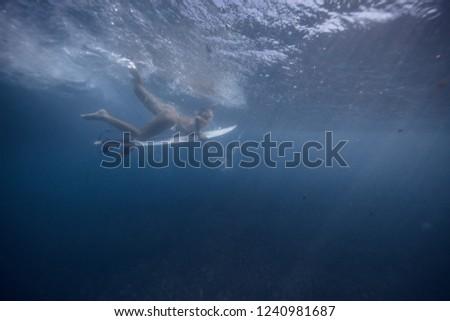 Stock Photo Surfing girl doing duck dive underwater in Bali ocean