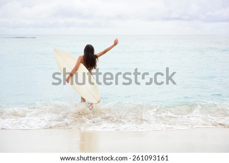 Surfing girl happy excited going surfing at ocean beach running into water. Female bikini woman heading for waves with surfboard having fun living healthy active lifestyle by sea. Water sports model.