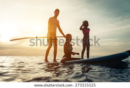 surfing. happy family silhouette on the paddle board. concept about family, sport and fun