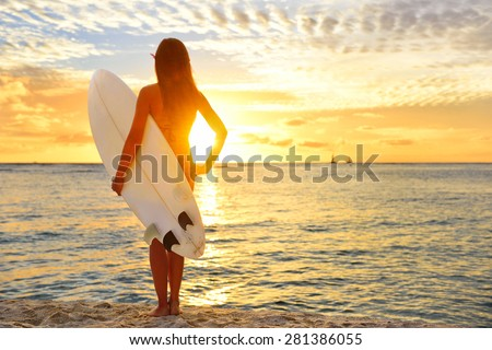 Surfing surfer girl looking at ocean beach sunset. Silhouette of female bikini woman looking at water with standing with surfboard having fun living healthy active lifestyle. Water sports with model.