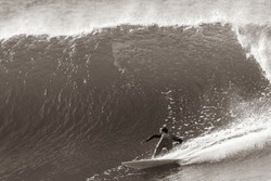 Surfing surfer unrecognizable bottom turning rear behind action on ocean wave under the curl in sepia black white tone photo
