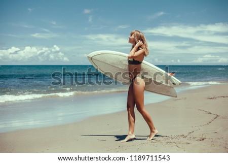 Stock Photo Surfing surfer woman babe beach fun at sunset. Girl walking in sunshine in warm evening sun holding surfboard. Water sport summer vacation travel concept. Kaanapali beach, Maui, Hawaii, USA