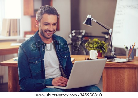 Surfing the net in office. Confident young man working on laptop and smiling while sitting at his working place in office