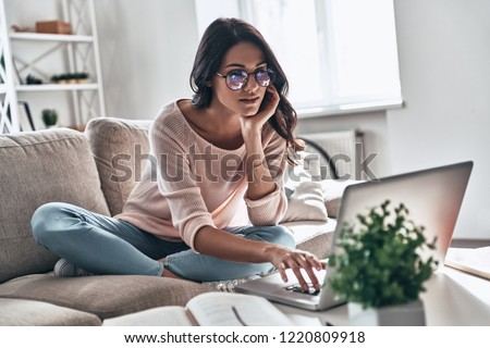 Surfing the net. Thoughtful young woman in eyewear using computer while sitting on the sofa at home