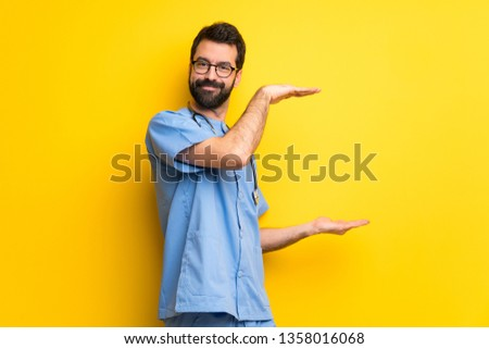 Surgeon doctor man holding copyspace to insert an ad