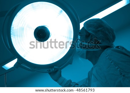 Surgeon moving the surgical reflector at the  operating room