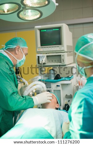 Surgeon putting an oxygen mask on a patient in a surgical room - stock photo