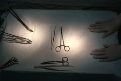 surgeon's hand, in sterile gloves, holds the instrument before performing diagnostic manipulations. Hands of a nurse in the operating room