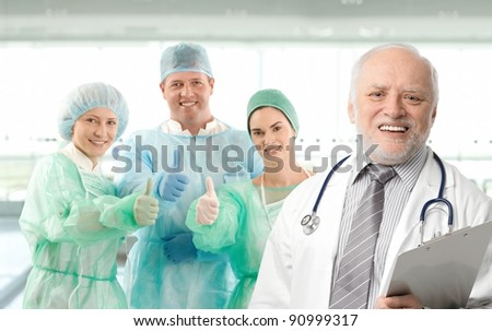 Surgeon team lead by senior white haired doctor looking at camera, smiling.?