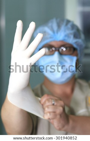 surgeon wears rubber glove in foreground with blurred face on background