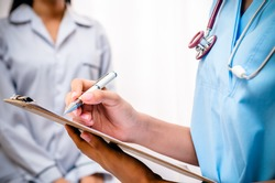 surgeon writing patientâ??s record after examine health