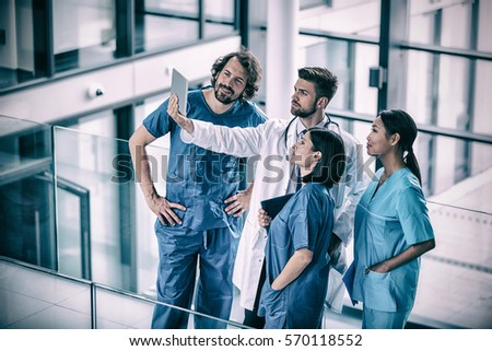 Surgeons, doctor and nurse looking at digital tablet in hospital